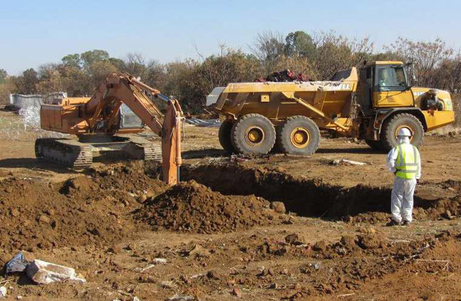 Excavating trench with HCRW Health Care Risk Waste.